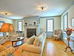 The second 'formal' Colonial-style living room has 2 comfortable couches and a fireplace with wainscoting.
