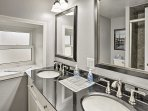 The second bathroom hosts a double vanity and walk-in shower.