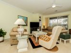 Comfortable and relaxing furniture invites conversation, and affords a view of the extended lanai.