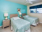 Guest bedroom with twin beds, 32-inch TV and DVD.
