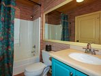 This guest bathroom contains a tub & shower, vanity and lots of space to store your personal belongings.
