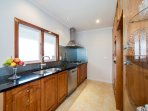 Modern kitchen with all necessary appliances and basic cooking condiments