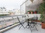Sunny, spacious balcony with a marble table for four