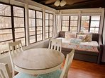 Sunroom and dining area comes serves as a second sleeping quarters with a twin day bed and trundle.
