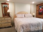 King bed with distressed wood headboard and posts, see the jazz fest poster on your right?
