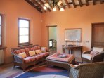 High ceilings, large windows onto the olive groves, antique maps, tables & armoires & designer rug..