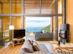 Open plan living room area with balcony & sea view in each villa