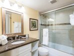 The guest bathroom includes a tub/shower and plenty of cabinet space for towels and toiletries.