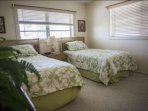 The welcoming, upstairs, guest bedroom offers 2 twin beds for 2 additional guests.