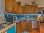 A vibrant blue backsplash lines this well-equipped kitchen.