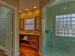 The master bathroom's walk-in shower boasts a spacious layout and bench.