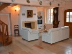 Grand salon tout équipé avec cheminée, canapés en cuir et télévision