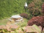 low level secluded seating area in garden accessed by large stone steps
