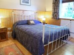 Large high ceiling spacious double bedroom with wardrobes and dressing table.