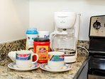 Coffee maker, coffee, sugar, and powdered coffee creamer are provided.