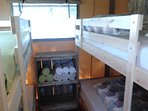 Two bunkbeds, one of the 3 bedrooms, with sliding doors.