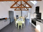 Open-plan living area with exposed beams and woodburner