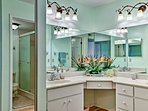 The en-suite bathroom features dual sinks, a large vanity mirror, and a stand-up shower.