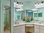 The en-suite bathroom features dual sinks, a vanity mirror, & stand-up shower.