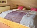 Ein weiteres Schlafzimmer mit Doppelbett und mit Waschgelegenheit befindet sich im Obergeschoß