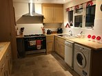 Kitchen with tassimo, dishwasher and washing machine / tumble dryer. Views out over rear garden.