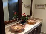 master bathroom with hand carved stone sinks