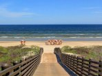 Bridge leading from the community to the beach. Umbrellas and seating can be...