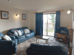 Curlew Lodge living room is practical and with lake views from the large patio doors to the balcony.