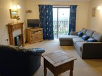 Kingfisher living room has a sofabed and lake views from the large patio doors to the balcony.