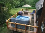large deck with hot tub, grill and seating
