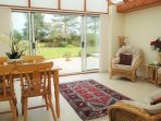 Conservatory with seating for 4 people overlooking the decking and back garden