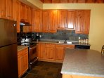 The modern kitchen is fully equipped and has stainless appliances.