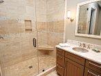 Il bagno adiacente ha una grande doccia piastrellata e due vanità in granito.