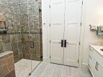 Il bagno privato ha un lavandino in granito e una grande cabina doccia piastrellata.