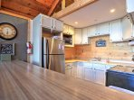 Stainless steel appliances and custom wood cabinets embellish the cooking space.