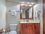 There is a single sink, small vanity, and shower/tub combo behind the door to the bedroom.