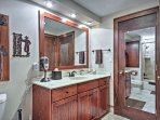 The first full bathroom has a single sink, large vanity mirror, and a shower/tub combo.