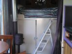 double bed above cab and fire, draws wardrobe behind sliding doors