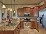 This fully equipped kitchen has granite countertops and stainless steel appliances.