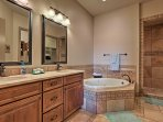 This en-suite bathroom has a walk-in shower and a jetted jacuzzi tub.
