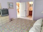master bedroom has a TV and attached ensuite bath with spa tub