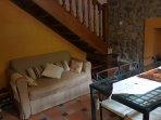 Salón con sillón y mesa , escaleras acceso 1ª planta