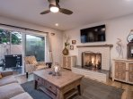 Unit A: Living room with TV, fireplace, and doors onto private patio
