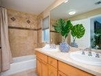 Master bathroom includes double sinks and shower/tub combination.