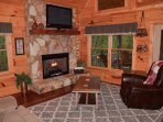 Relax by the stone fireplace and enjoy one of two large flat screen TVs.