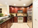The tile-floored, fully equipped kitchen provides ample counter space and the essential appliances for preparing...
