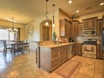 The kitchen comes fully equipped with granite counters, stainless steel appliances, and wood cabinetry.
