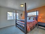 Sunlight pours into the second bedroom, which features a queen bed.