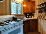 The kitchen area is fully equipped with all cooking and dining essentials.