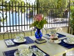 Table in the garden close to the lake for sunset dinner and alfresco breakfast